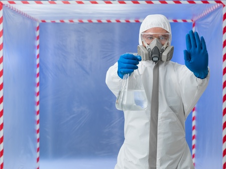 person in biohazard protective suit wearing a breathing mask calling a halt by raising one hand while holding a bottle of transparent colorless liquid in the other standing in front of a containment tent