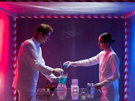 two scientists, a man and a woman, working with chemicals in a containment tent, lit by a gradient red and blue light photo