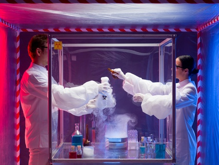 two scientists, a man and a woman, mixing chemicals in a sterile chamber, holding a glass container labeled as bio hazardous filled with white pouring steam, containment tent photo