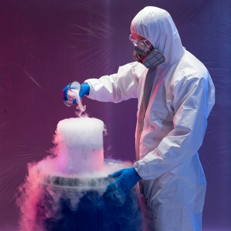 hazardous: person in a protective suit and gas mask working with steaming substances over a blue waste drum inside a containment tent