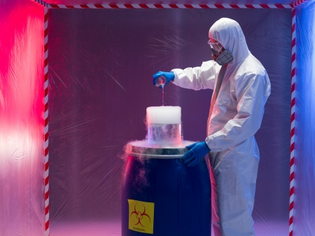 containment: person in a protective suit and gas mask experimenting with steaming substances over a blue plastic waste container inside a containment tent Stock Photo