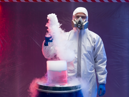 person in a protective suit and gas mask experimenting with steaming substances over a blue plastic waste barrel inside a containment tent photo