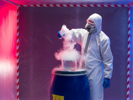 person in a protective suit and gas mask experimenting with steaming substances over a blue plastic waste barrel marked as bio hazardous inside a containment tent Stock Photo