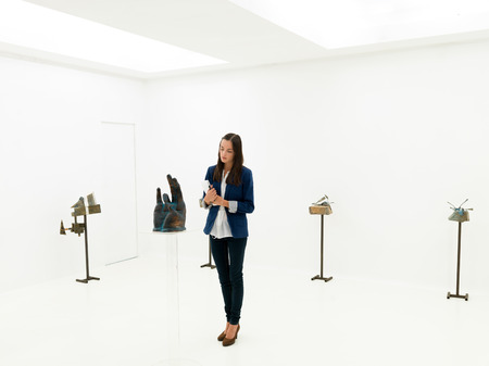 curator: young caucasian art collector looking at contemporary sculptures displayed in a white exhibition space