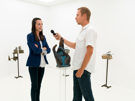 handsome caucasian man interviewing a woman in an art gallery photo