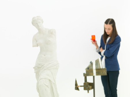 woman scrutinizing sculpture behind a replica of Venus de Milo statue in a museum photo