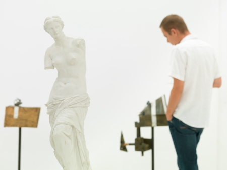 man looking at contemporary sculpture behind a replica of venus de milo in a museum photo