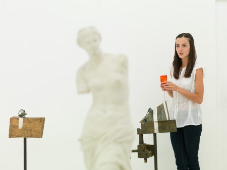 venus symbol: young caucasian woman standing in front of an artwork, holding a glass of wine in her hand, speaking, in an art museum Stock Photo