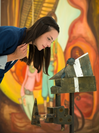 side view of woman closely scrutinizing a contemporary sculpture placed in front of colorful large painting photo