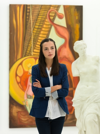 art gallery: cropped view of woman standing in a museum with her arms crossed, looking at a statue
