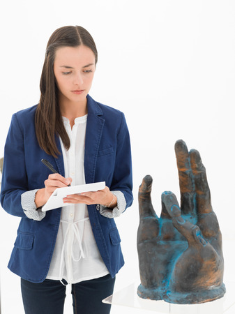 take a note: front view of woman taking notes about an artwork, in a museum Stock Photo