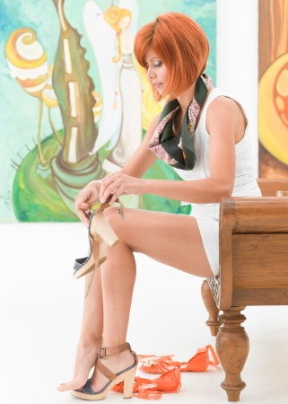 changing seasons: side view of young beautiful redhead woman sitting on a wooden bench changing her shoes Stock Photo