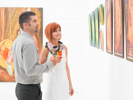 appreciating: young caucasian couple standing in a gallery and holding glasses of wine in their hands, contemplating artwork displayed on walls Stock Photo