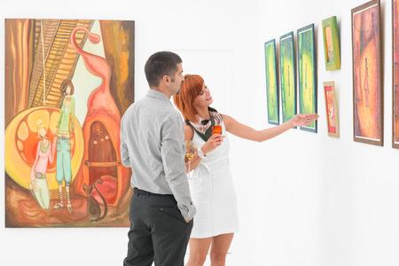 若い魅力的な女性は、アート ギャラリーの壁に表示されるいくつかのアートワークを指して、男の隣に立っています。 写真素材