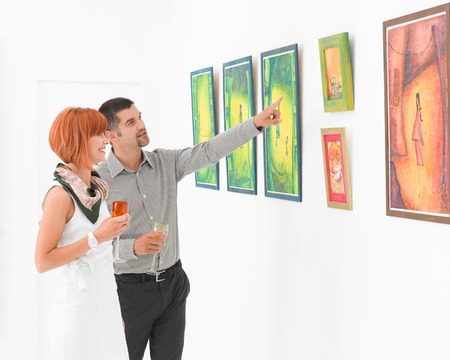 handsome man standing in an art gallery next to a redhead attractive woman, pointing at some framed paintings