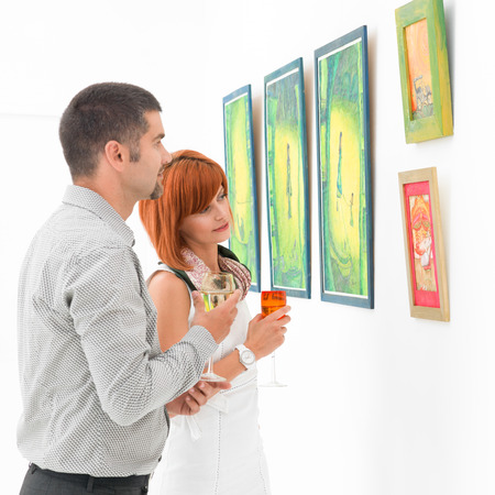 two young caucasian people standing in front of colorful framed paintings, contemplating them photo