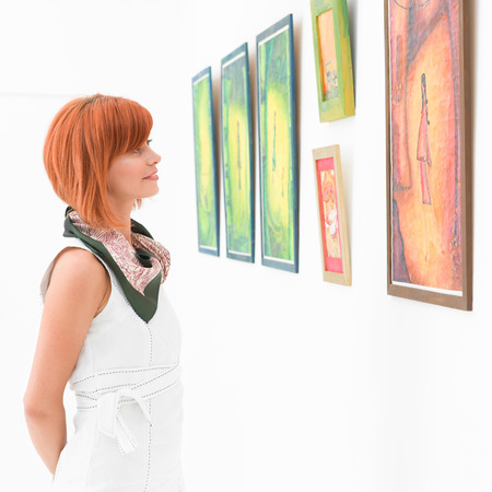 side view of young attractive redhead woman standing in an art gallery contemplating an artwork Standard-Bild