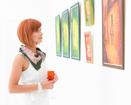 young caucasian redhead woman standing in a museum admiring colorful framed paintings photo