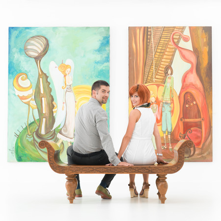 young couple sitting on a wooden bench in front of large colorful paintings holding hands and smiling photo
