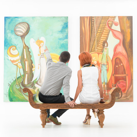 young caucasian couple sitting on a wooden bench in an art gallery pointing at some painting