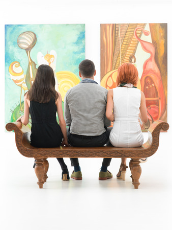 back view of three young people sitting on a wooden bench in a museum admiring large paintings photo