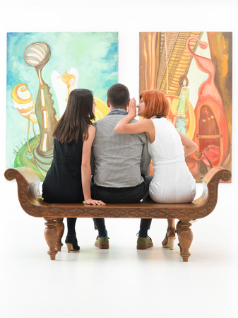 admiring: young people sitting on bench in front of two large paintings gossiping
