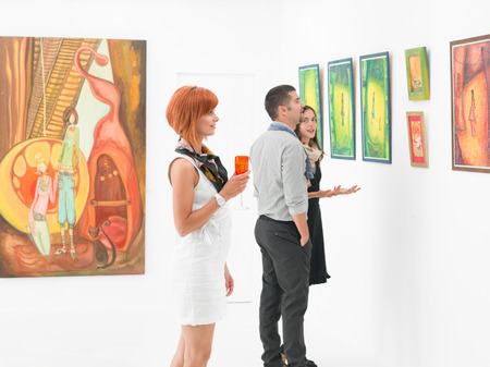 아트 갤러리에서 젊은 백인 사람들이 그림을보고 그들에 대해 이야기