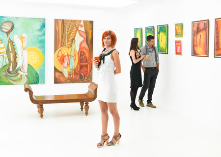 beautiful caucasian woman standing in an art gallery with other people contemplating art  版權商用圖片