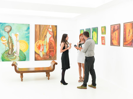 interviewed: young caucasian woman being interviewed by two people holding a recording device, in an art gallery