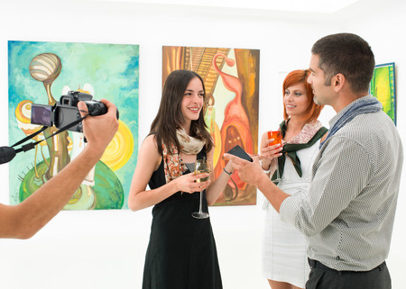 woman being interviewed and photographed in an art gallery Stock Photo