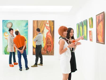 壁に表示されるカラフルな絵画について話して、アート ギャラリーの人々