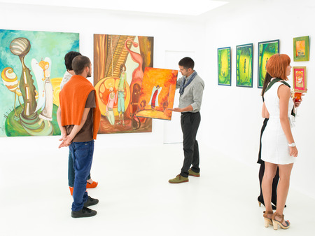 art work: man holding and showing a colorful painting to other people in an art gallery
