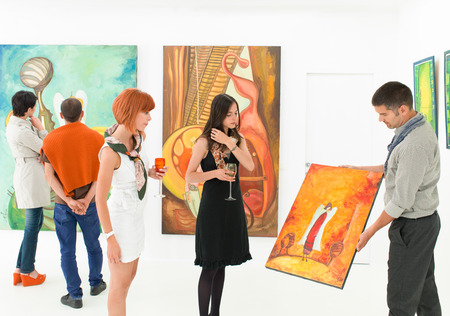 auctioning: man holding and showing a colorful painting to other people in an art gallery