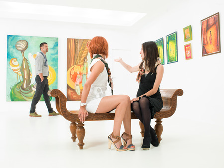women sitting on a bench in an art gallery talking about a man thats visiting the exhibition