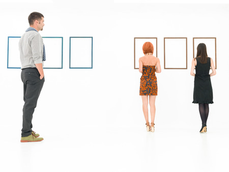 people in a white room looking at empty frames displayed on walls Standard-Bild