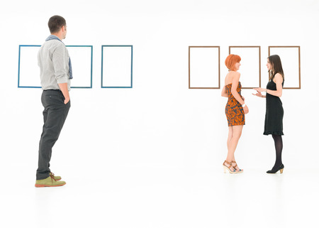 admiration: caucasian people standing in a white room talking and looking at empty frames displayed on walls
