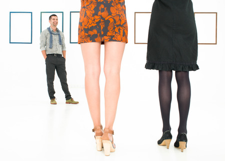 back view of women legs in a white room, standing in front of a man and empty frames on walls photo