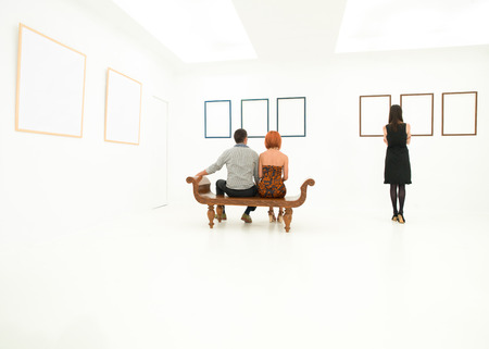 back view of three young caucasian people looking at empty frames on white walls