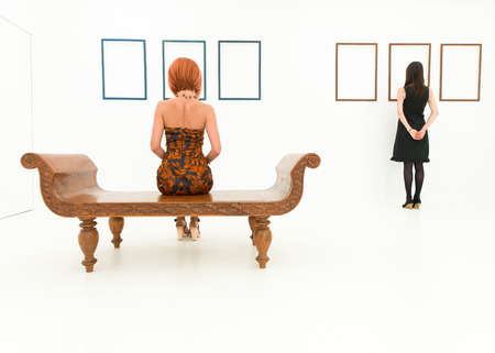 art gallery: rear view of two women in a white room looking at empty frames displayed on walls in front of them