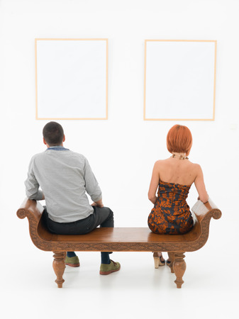 rear view of man an woman sitting on a wooden bench looking at empty frames displayed on a white wall in front of them photo