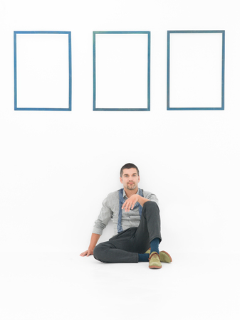 sitting rooms: front view of man sitting on the floor in a relaxed posture against a white wall with three empty blue frames Stock Photo