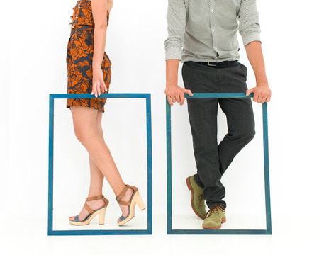 cropped view of man and woman legs behind two empty frames photo