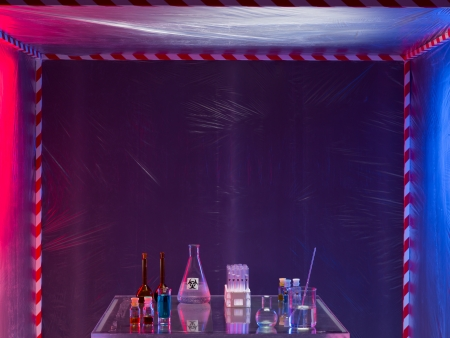 containment: different glass containers filled with differently colored liquids on a glass table in a containment tent, placed outdoors, by night, lit on opposite sides by a red and a blue light Stock Photo