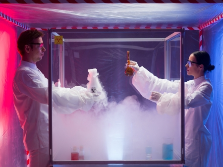 two scientists, a man and a woman, mixing chemicals in a sterile chamber labeled as bio hazardous filled with white steam, in a containment tent photo