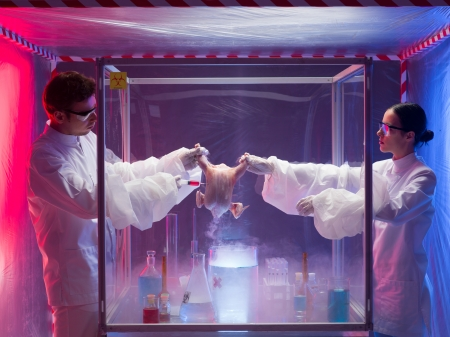containment: two scientists, a man and a woman, conducting chemical experiments on a raw chicken in a protection enclosure, in a containment tent