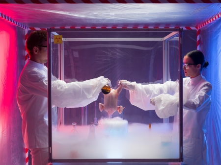 two scientists, a man and a woman, the man pouring a chemical substance on a raw chicken in a protection enclosure filled with fumes, in a containment tent photo