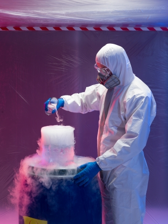 containment: person in a protective suit and gas mask working with steaming substances over a blue waste plastic container inside a containment tent Stock Photo
