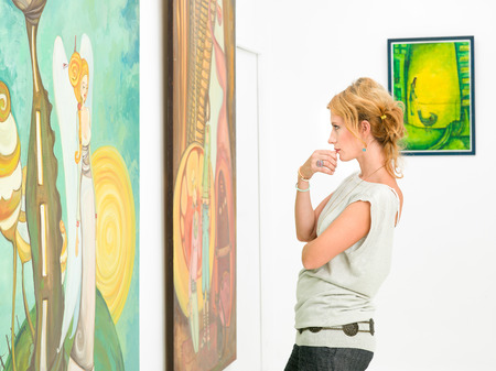 side view of young beautiful woman standing in an art gallery contemplating paintings displayed in front of her photo