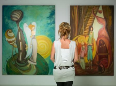 achteraanzicht van younga blanke vrouw stading in een kunstgalerie in de voorkant van twee grote kleurrijke schilderijen