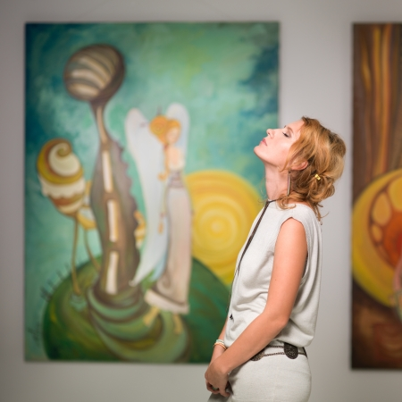 side view of woman standing in an art gallery with her eyes closed and her head facing up